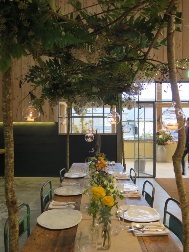 inside venue with trestle tables and floral decor