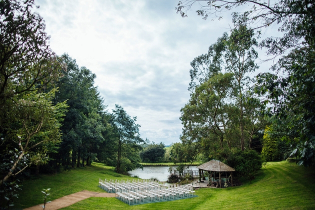 gazebo and ceremony chairs by a lake surrounded by trees