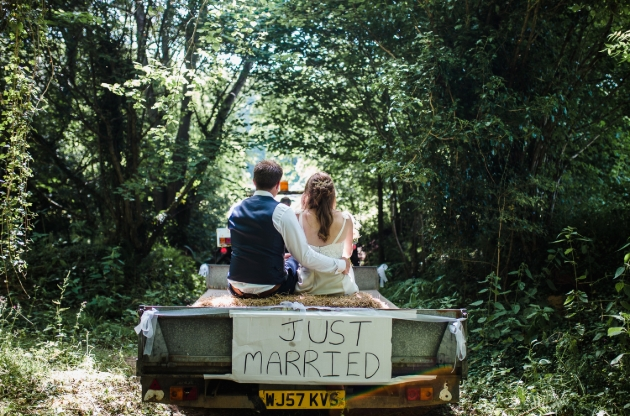 couple in wedding outfits sat on back of open top jeep with sign just married