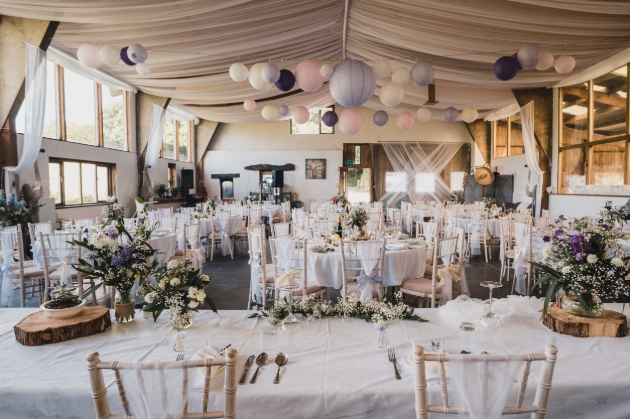 interior of barn set up for wedding reception tables and chairs decorated