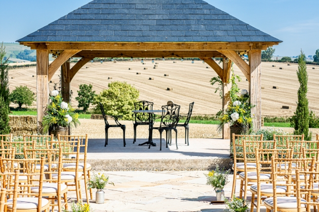 gazebo with wedding chairs and fields in background on sunny day
