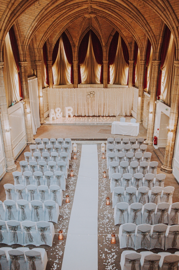 inside the historic chapel with ceremony chairs set up for wedding under sweeping pillars and high ceiling